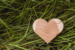 Heart shape carved in wood lies on a green grass. Stock Photography