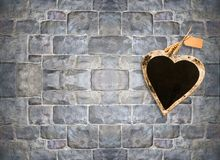 Heart shape chalk board on stone brick wall.  stock photos