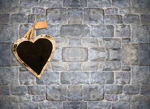 Heart shape chalk board on stone brick wall. With copy space royalty free stock image