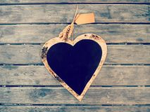 Heart shape chalk board on wooden wall. Vintage color filtered royalty free stock photo
