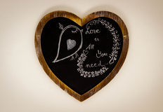 Heart Shape Chalk drawing - Love is all you need. Heart Shape Drawing On Chalk Board with bird - Love is all you need royalty free stock photo
