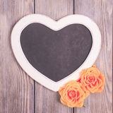 Heart shape chalkboard. And yellow roses over wooden background Royalty Free Stock Photo