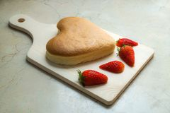 Heart shape cheese cake with strawberry on wooden chopping board for valentine`s day. Heart shape cheese cake with strawberries on wooden chopping board for royalty free stock images