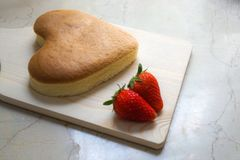 Heart shape cheese cake with strawberry on wooden chopping board for valentine`s day. Heart shape cheese cake with strawberries on wooden chopping board for stock image