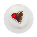 Heart shape chocolate cake with sugare red heart on white plate, wood background, close up, isolated Royalty Free Stock Image