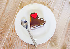 Heart shape chocolate cake with sugare red heart on white plate, wood background, close up, isolated Royalty Free Stock Photo