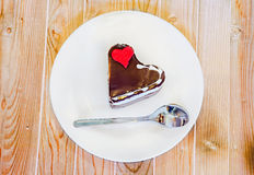 Heart shape chocolate cake with sugare red heart on white plate, wood background, close up, isolated Stock Photo