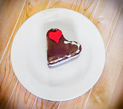 Heart shape chocolate cake with sugare red heart on white plate, wood background, close up, isolated Stock Images
