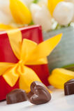 Heart shape chocolates, red gift and tulips Royalty Free Stock Photography