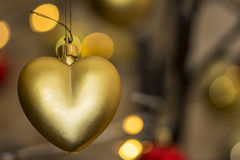 Heart shape christmas decoration with bokeh lights. Heart shape christmas bauble hanging from contemporary christmas tree Stock Images
