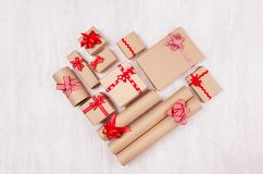 Heart shape of christmas presents of craft paper gifts with red ribbons and bows on soft light white wood board, flat lay. royalty free stock image