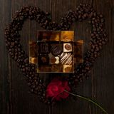 Heart shape  from coffee beans and a box of chocolate pralines Stock Photography