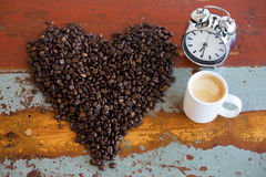 Heart shape coffee beans and cup of coffee and alarm clock Royalty Free Stock Photo