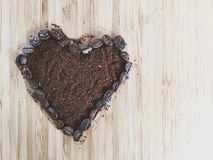 Heart shape coffee beans and ground coffee with copy space Stock Image