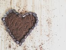 Heart shape coffee beans and ground coffee messy with copy space Stock Photography