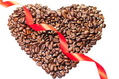 Heart shape coffee beans with a red ribbon across Stock Photos