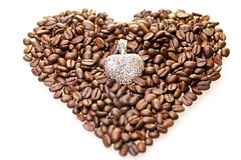 Heart shape coffee beans with a silver pendant Stock Photos