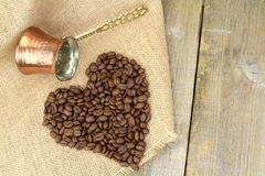 Heart shape with coffee beans and traditional Turkish copper coffee pot on a burlap Stock Photography