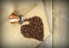 Heart shape with coffee beans and traditional Turkish copper coffee pot on a burlap Stock Image