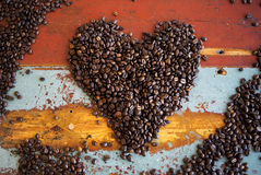 Heart shape of coffee beans on wooden table Royalty Free Stock Image