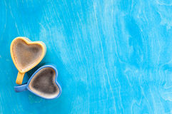 Heart shape coffee cup on wooden table. Two cups heart on a blue wooden background Royalty Free Stock Image