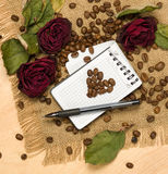 Heart shape from coffee seeds on blank sheet and red roses Stock Photography