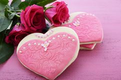 Heart shape cookies decorated as pink ladies dresses with bouquet of pink roses Royalty Free Stock Photo