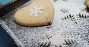 Heart shape cookies with snowflake and icing sugar on tray stock video footage