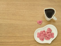 Heart shape of cup with coffee and heart shape of plate with pink sweet hearts in white plate. Love coffee. Top view. Happy Valent Stock Photo
