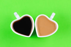 Heart shape cups on green background Royalty Free Stock Images