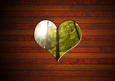 Heart Shape cut on Brown Wooden Wall. Brown wooden wall with a hole in the shape of heart and forest of pine and beech Stock Photo
