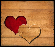 Heart Shape cut on Old Wooden Boards. Brown wooden wall with a hole in the shape of heart and red velvet background with roses flowers Stock Photo