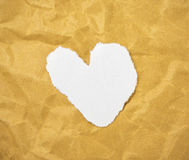 Heart shape in cut out magazine letters put on brown paper. Royalty Free Stock Photography