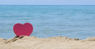 Heart shape dipped in sandy beach with the look at horizon Royalty Free Stock Photos