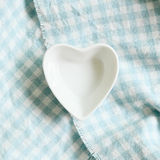 Heart shape dish on light blue check pattern cloth background. Top view Stock Photos