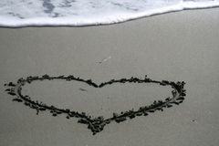Heart shape drawing on the sand. Heart shape drawing on the dark wet sand with a foamy wave on the background on Dasoudi beach in Limassol, Cyprus royalty free stock image