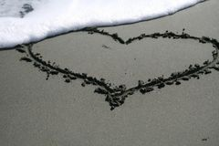 Heart shape drawing on the sand. Heart shape drawing on the dark wet sand with a foamy wave that washing it away on Dasoudi beach in Limassol, Cyprus royalty free stock photos
