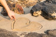 Heart shape drawing on the white sand nature between the rock, love in rock. summer trip royalty free stock image