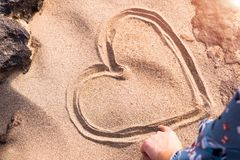 Heart shape drawing on the white sand nature between the rock, love in rock. summer trip stock image