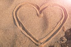 Heart shape drawing on the white sand nature between the rock, love in rock. summer trip stock photos