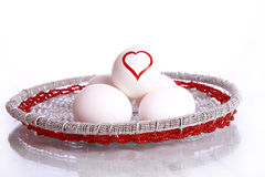 Heart shape drawn on egg. S standing over other eggs , and place over beautiful royal vessel , isolated against white background Royalty Free Stock Images