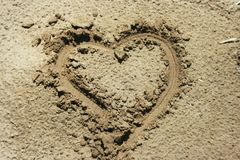 A heart shape drawn in the sand Stock Photos