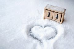 Heart shape drawn on snow close-up view from above, winter background royalty free stock photo