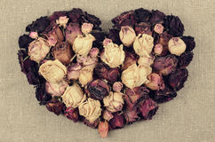 Heart shape from dry roses on linen canvas background Stock Photography