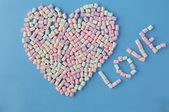 Heart shape figure from colored marshmallow on blue background Stock Photography