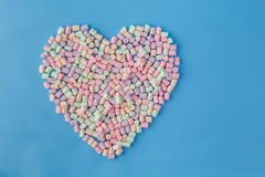 Heart shape figure from colored marshmallow on blue background Stock Photos