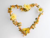 Heart shape flower wreath. Plastic orange and yellow spring flowers, white background Royalty Free Stock Photos