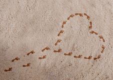 Heart shape with footprints on the sand Royalty Free Stock Image