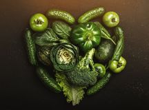 Heart shape form by various green healthy vegetables, top view.  Royalty Free Stock Photo
