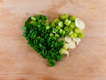 Heart shape formed from bunch onion on wood. Big heart shaped pile of bunching onion on the wooden board, from the top view, healthy life style Royalty Free Stock Images